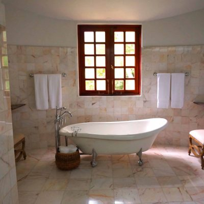 Canva - White Bathtub on White Tile Bathroom Near Brown Framed Clear Glass Window